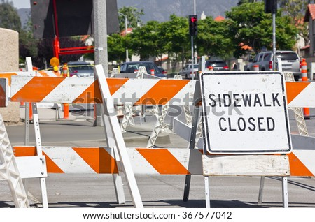 Sign shows that the sidewalk is closed and construction can be seen next to the street.