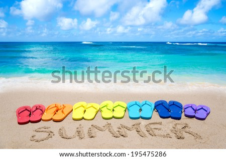 """Sign """"Summer"""" and color flip flops on sandy beach by the ocean in sunny day - stock photo"""