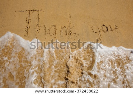 Sign Thank you on the sandy beach next to ocean washed by wave  - stock photo