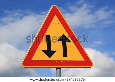 Sign two way traffic against blue sky with some clouds. - stock photo