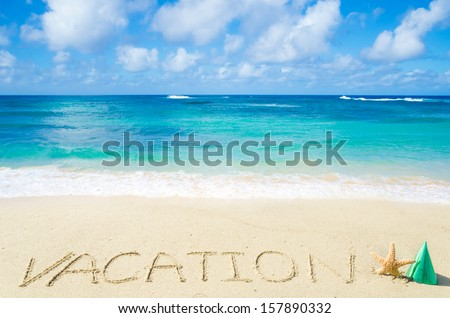 "Sign ""Vacation"" on the sandy beach by the ocean"