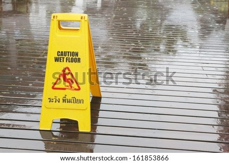 Sign warning of a slipping due to rain on a wooden floor - stock photo