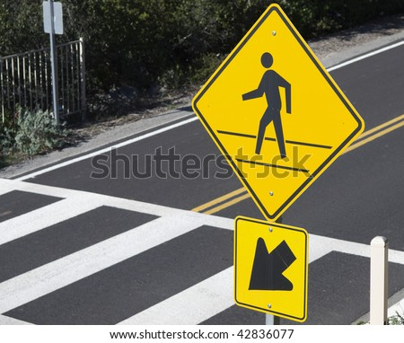 Sign warning of pedestrian crossing and crosswalk in California. Selective focus on sign.