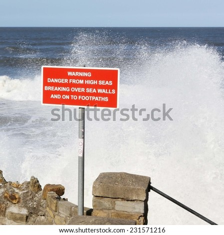 Sign warning of the danger of heavy seas in front of breaking waves.  - stock photo