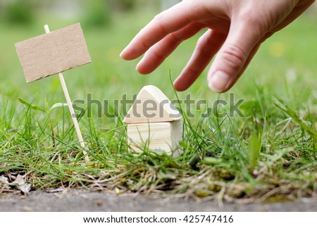 signboard standing near the house to which the stretches a hand / offer great demand - stock photo