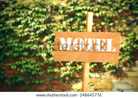 Signboard with text Motel on brick wall background - stock photo