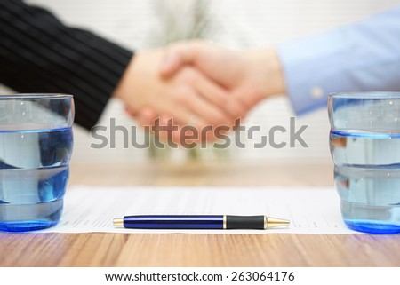 signed contract with handshake in blur, focus on pen - stock photo