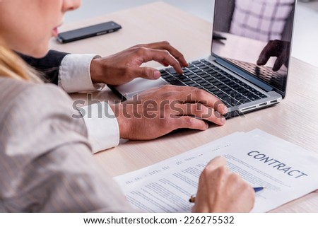 Signing a business contract. Two successful businessman smiling and looking at the laptop while businessmen sitting at a table working on a laptop on a gray background close-up view. - stock photo