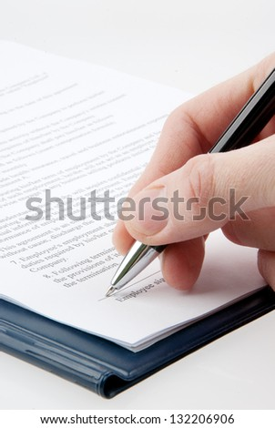 Signing a contract by a hand isolated on white background