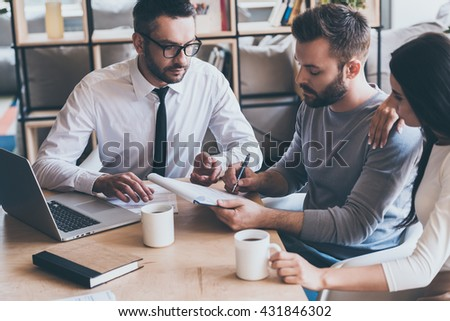 Signing contract. Confident young man signing some document while sitting together with his wife and man in shirt and tie  - stock photo