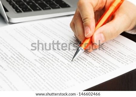 Signing Contract with orange pen, laptop and male hand - stock photo