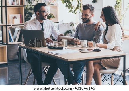 Signing good condition contract. Cheerful young man signing some documents while sitting at the desk together with his wife and man in shirt and tie  - stock photo