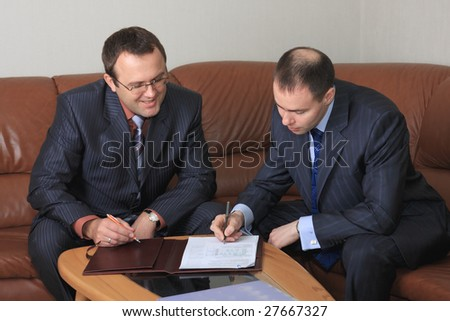 Signing of agreement two businessmen is in an office.