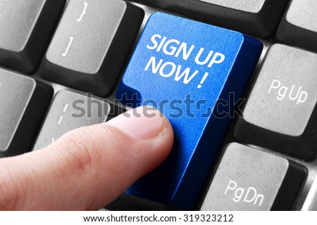 Signing up. gesture of finger pressing sign up now button on a computer keyboard - stock photo