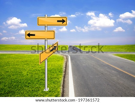 signpost direction pole beside road with fresh green grass and blue sky in bright day - stock photo
