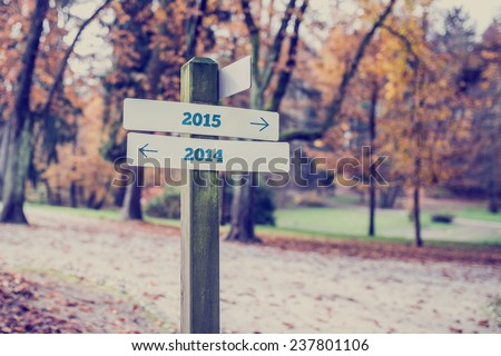 Signpost in a forested area with arrows pointing two opposite directions towards year 2014 and 2015. - stock photo