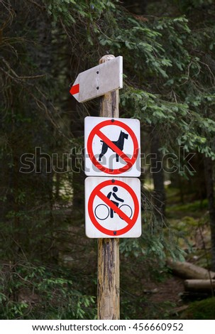 """Signpost in park with warning """"no ride bikes and no dogs allowed"""".  - stock photo"""