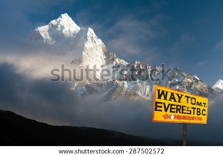 signpost way to mount everest b.c. and evening himalayan panorama with mount Ama Dablam - stock photo