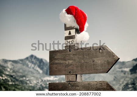 Signpost with Santa Hat - Signpost with Santa Hat in front of a mountain landscape.  - stock photo