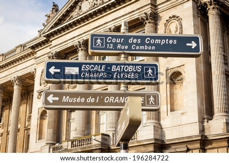 Signposts in Paris centre pointing the way to a museum, an audit court and the Champs Elysees with the steps to the Batobus which takes tourists for trips on the Seine River - stock photo