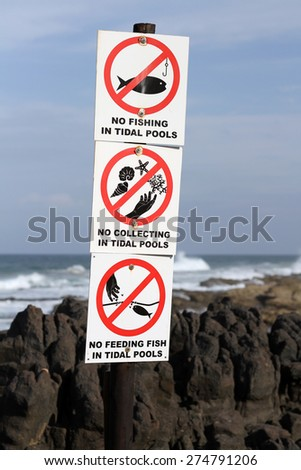 Signs on a beach enforcing various rules. - stock photo