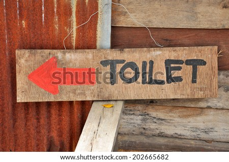 Signs to the toilets, which was written on a sheet of plywood. - stock photo