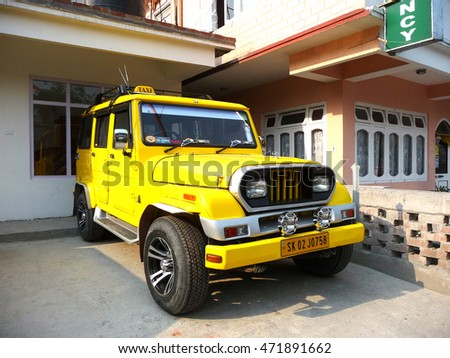 SIKKIM/ INDIA-APRIL 13, 2013: A smart yellow taxi jeep car parking at a house.