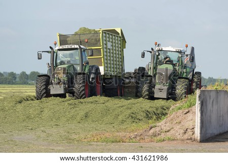 silage with two tractors and a car - stock photo