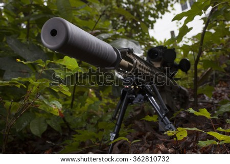 Silencer on a rifle seen from the front in some trees - stock photo