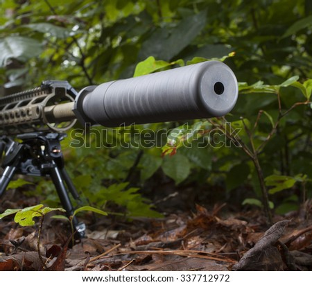 Silencer on the end of a rifle barrel that is in some trees