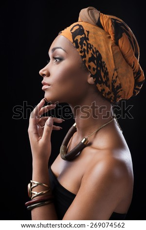 Silent beauty. Side view of beautiful African woman wearing headscarf and touching chin by her finger while standing against black background - stock photo