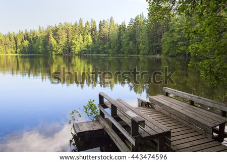 Silent evening at the pier. An image of an empty pier by the lake. Sun is about to go down in Finland. - stock photo