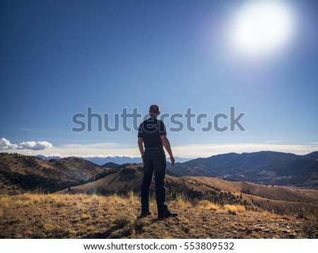 Silhouet of man standing on top of mountain overlooking beautiful landscape