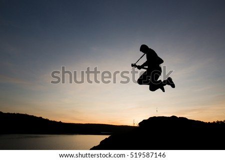 Silhouette a man jumping with playing guitar in the sunset or sunrise