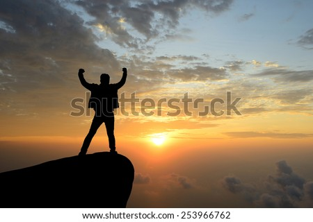 silhouette achievements successful arm up man is on top of hill celebrating success with sunrise - stock photo