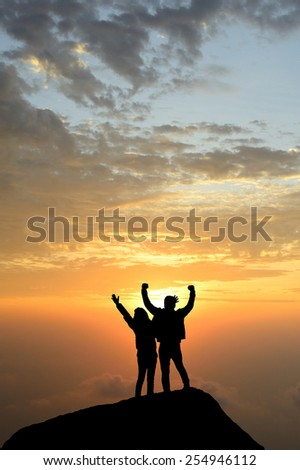 silhouette achievements successful both arm up couple is on peak of hill celebrating success with sunrise - stock photo