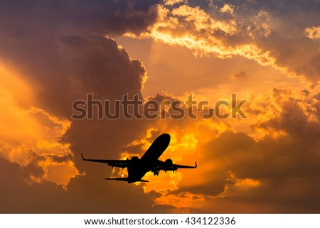 Silhouette airplane flying take off on sunrise background. - stock photo