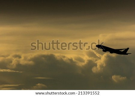 Silhouette airplane in the sky - stock photo