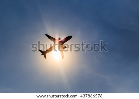Silhouette airplane taking off over blue sky at sun background