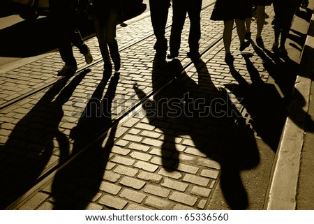 Silhouette and shadows of people walking, brick pavement and street car tracks, focus on shadows, Fisherman's Wharf, San Francisco, California,