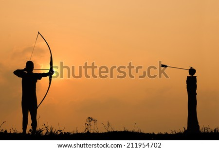 Silhouette archery shoots a bow at an apple on timber in sunset sky and cloud.  - stock photo