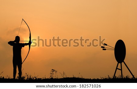 Silhouette archery shoots a bow at the target in sunset sky and cloud. - stock photo