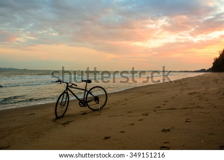 Silhouette bike with sunset sky at sea - stock photo