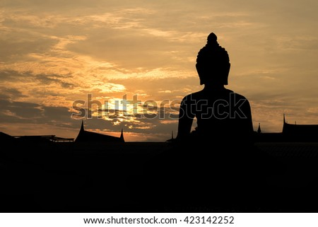 Silhouette,blurry,art tone of temple with big buddha statue with beautiful evening sky background - stock photo
