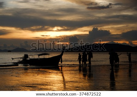 Silhouette boat and tourist at beach during sunset  - stock photo