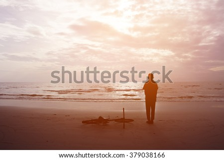 Silhouette boy standing on the beach - stock photo