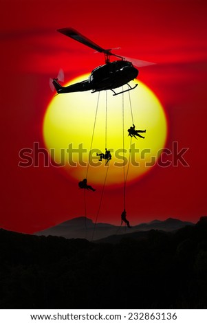 Silhouette Brave soldiers operating out assault by soldiers rappelling from a helicopter to fly at Mountain evening sun on the horizon dark red sky. - stock photo