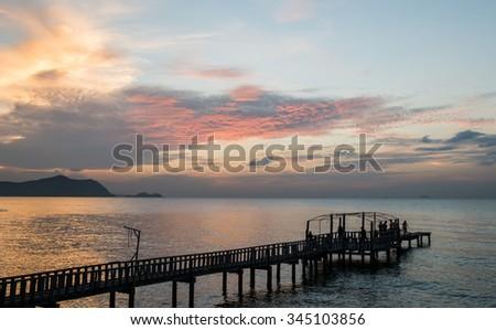 Silhouette Bridge and pavilion on the sea with people walk on the bridge - stock photo