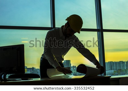 Silhouette builder engineer wear security helmet look at blueprint paper construction drawing plan on background of sunset window frame blue yellow sky with clouds near pc monitor computer