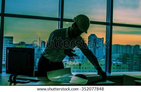 Silhouette builder engineer wear security helmet stock photo silhouette builder engineer wear security helmet look at blueprint paper construction drawing plan on background of malvernweather Image collections